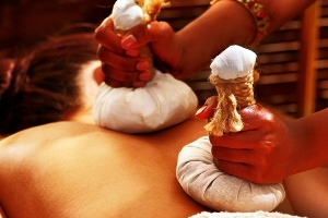 lady receiving a pindasveda hot-poultice ayurvedic massage